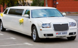 White wedding limousine on the road. Ornated with flowers.